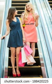 Shopping together is fun. Two girls standing on escalator and carrying shopping bags