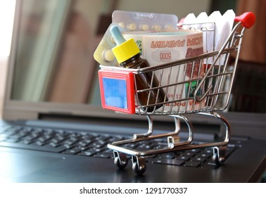 Shopping trolley with blisters of medical pills and   bundle of money russian rubles on opened laptop. Medicine cost concept.