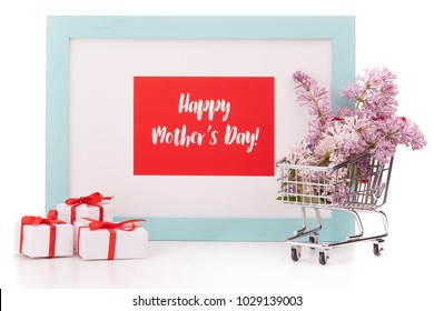 Shopping trolley with brenches of Lilac, gift boxes and frame with blank space on white background. Copy space for adding your content.  Advertising. Greeting card. Mothers day.