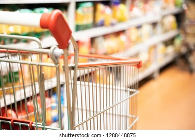 Shopping trolley cart with shallow DOF against modern supermarket aisle blurred background