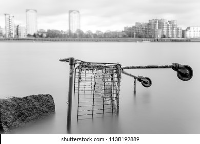 Shopping Trolley Cart sideways in the river Thames with a rock in the foreground and city buildings in the background in black and white, long exposure shutter speed duration in London UK