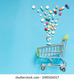 Shopping trolley cart w/ assorted medicine pills on light blue background. Creative idea for drugstore, online pharmacy, health behaviors and pharmaceutical company business concept. Flat layout.