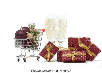 Shopping trolley, champagne flutes, gift boxes and Christmas decoration isolated on white  background, Christmas and New Year shopping. Winter sale.