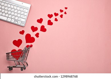 Shopping trolley, Computer keyboard and  decorative red hearts on pink background with copy space. Concept of internet shopping. Valentine's day, Mother's day, wedding
