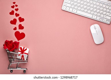 Shopping trolley, Computer keyboard and mouse, gift box, flower and decorative red hearts on pink background with copy space. Concept of internet shopping. Valentine's day, Mother's day, wedding