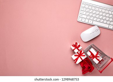 Shopping trolley, Computer keyboard and mouse, gift boxes on pink background. Top view with copy space. Concept of internet shopping. Valentine's day, Mother's day, wedding