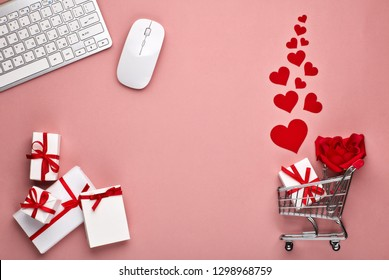 Shopping trolley, Computer keyboard and mouse, gift boxes, flower and decorative red hearts on pink background with copy space. Concept of internet shopping. Valentine's day, Mother's day, wedding