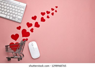 Shopping trolley, Computer keyboard and mouse, decorative red hearts on pink background with copy space. Concept of internet shopping. Valentine's day, Mother's day, wedding