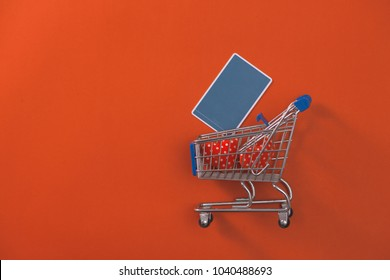 Shopping trolley with credit card on red background.