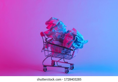 Shopping trolley with crumpled paper balls in trendy neon light. Gradient pink-blue glow. Concept art. Minimalism