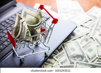 Shopping trolley with dollars on a laptop. Online sale.