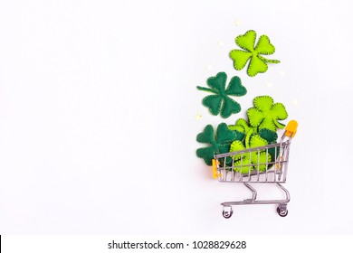 Shopping trolley with four-leaf clover on whte background. Copy space. St.Patrick's day holiday sale.