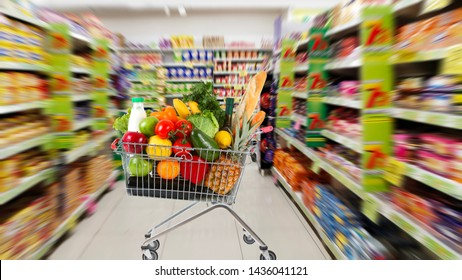 Shopping trolley full of fruits and vegetables against blurred backdrop of shopping mall area