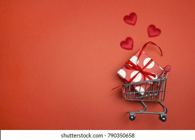Shopping trolley with gift box, love hearts  and cope space on red background.  St. Valentine's Day shopping and sale.
