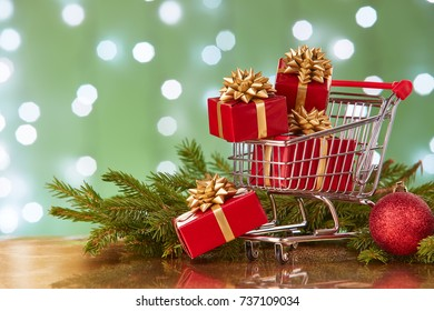 Shopping trolley with gift boxes and brenches of fir-tree with decoration on a green background with light of garland. Christmas and New Year sale.