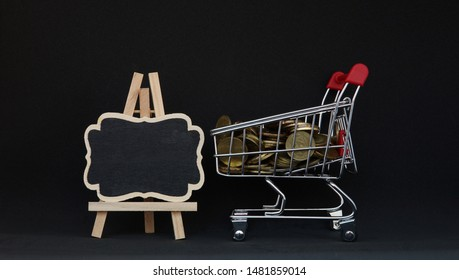 shopping trolley gold coins with Mock-up black chalk board on black background