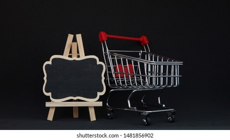 shopping trolley with Mock-up black chalk board on black background