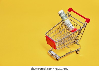 shopping trolley with money on yellow backgroud