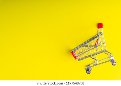 Shopping trolley on colorful background with some copy space with selective focus and crop fragment