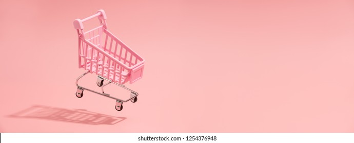 Shopping trolley on pink background
