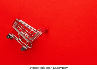 shopping trolley on red background with some copy space