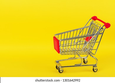 Shopping trolley on yellow background and some copy space.