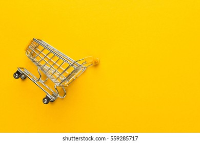 shopping trolley on yellow background with some copy space