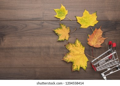shopping trolley over wooden background. overturned pushcart and yellow autumn leaves with some copy space. red shopping cart on brown table fall sale concept