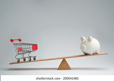Shopping trolley and piggy bank balancing on a seesaw