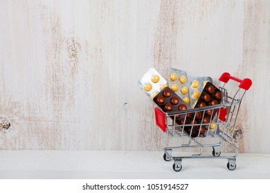 Shopping trolley with pills on a wooden background. Paid medicine. Purchase of medicines.