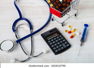 Shopping trolley with pills,money and calculator on a wooden background. Paid medicine. Purchase of medicines.