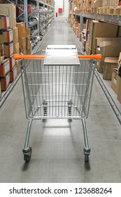 Shopping trolley in warehouse row with boxes