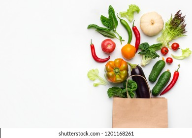 Shopping vegetarian food supermarket concept. Healthy vegetables in paper bag on white background, top view, copy space