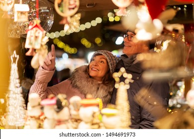 shopping, winter holidays and people concept - happy senior couple at christmas market souvenir shop on town hall square in tallinn, estonia