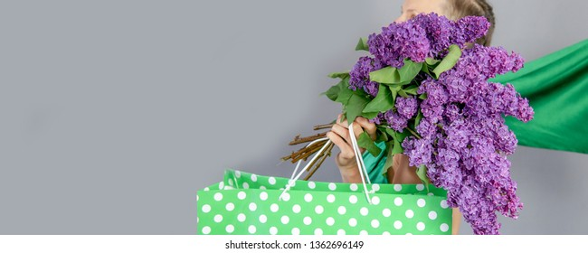 Shopping woman with shopping bag and huge bouquet of lilac