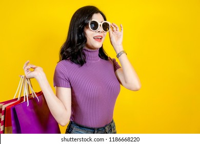 Shopping Woman concept, portrait or isolated an beautiful Asian woman wearing dress, hat and sunglasses with holding shopping bags and credit cards.