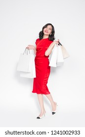 Shopping Woman concept, portrait or isolated an beautiful Asian woman wearing dress holding shopping bags