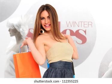 Shopping woman in front of winter sales window