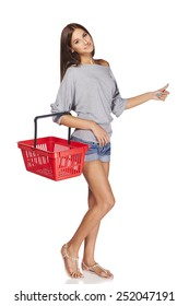 Shopping woman. Full length casual young woman standing smiling with empty shopping cart basket and gesturing thumb up sign, over white background