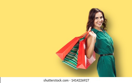 Shopping woman. Happy excited girl in green dress, holding bags, yellow color background. Copy space for some slogan, advertising or text. Consumerism and sales ad concept. Banner composition.