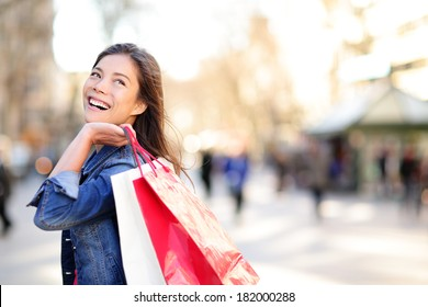 Shopping woman happy and looking away at copy space outdoors. Shopper girl holding shopping bags up excited outside on walking street. Mixed race Asian Caucasian female model on La Rambla, Barcelona.