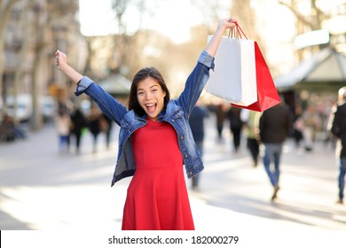 Shopping woman happy on La Rambla street Barcelona. Shopper girl holding shopping bags up excited outdoors on walking street. Mixed race Asian Caucasian female model cheerful in Spain.