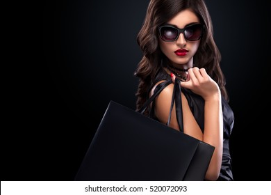Shopping woman holding grey bag isolated on dark background in black friday holiday