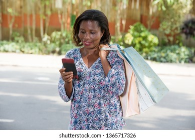 Shopping woman laughing while looking at the screen of her portable device. African woman looking for online store for shopping in town.
