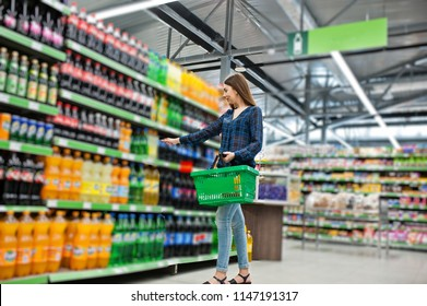 Shopping woman looking at the shelves in the supermarket.  Portrait of a young girl in a market store holding green shop basket and soft drink bottle.