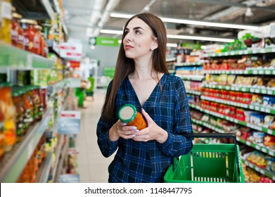 Shopping woman looking at the shelves in the supermarket.  Portrait of a young girl in a market store holding green shop basket and can of vegetables.