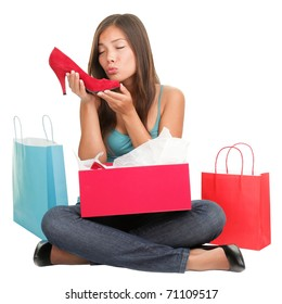 Shopping woman loves shoes. Funny cute image of young woman kissing high heels shoes after shopping. Asian Caucasian woman sitting isolated on white background.