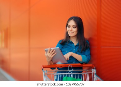 Shopping Woman with PC Tablet and Pushcart Near Store. Shopper girl online shopping and paying