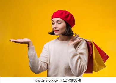 Shopping woman showing something with open hand palm. Happy girl holding shopping bags. Fashion woman shopper isolated on yellow background. Pretty woman in red beret. Copy space. Seasonal sales