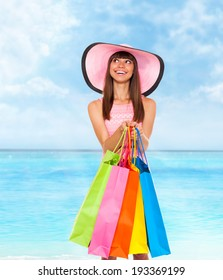 shopping woman summer vacation, hold colorful bags look to copy space over blue sky ocean background, wear pink dress and hat happy smile, young girl shop tour